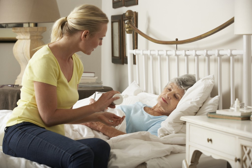 Adult Daughter Giving Senior Female Parent Medication In Bed
