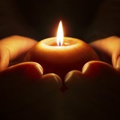 prayer - candle in hands in the darkness