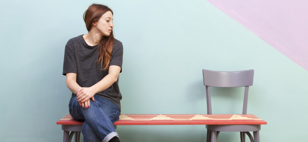 A beautiful redhead woman sitting along in a red bench