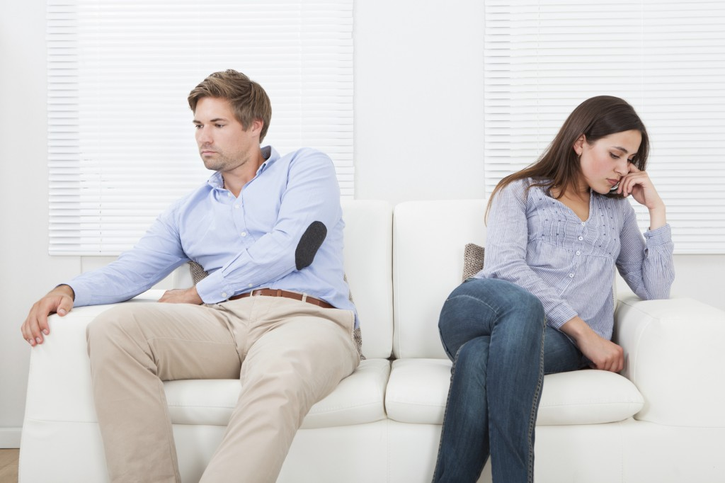 Couple sitting on a couch ignoring each other