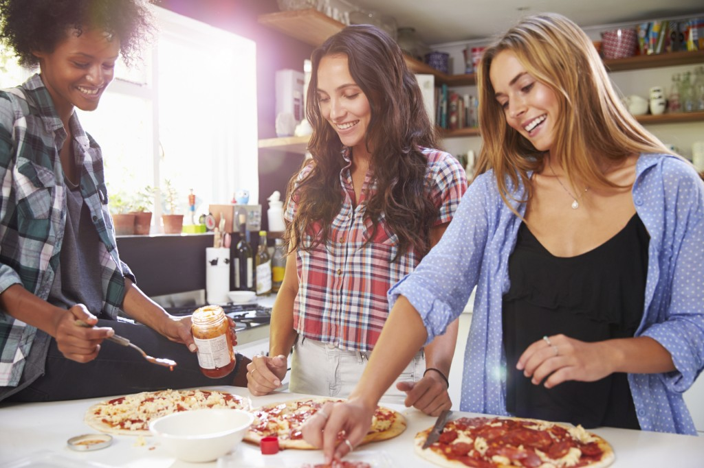 Three Female Friends Making Pizza In Kitchen Together, Smiling