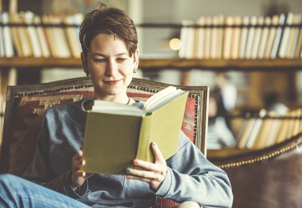 Young beautiful woman reading a book. Toned picture