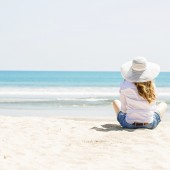 Beautifil young woman sitting on the beach at sunny day