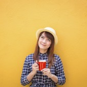 smiling woman wear in dress and hat holding red cup