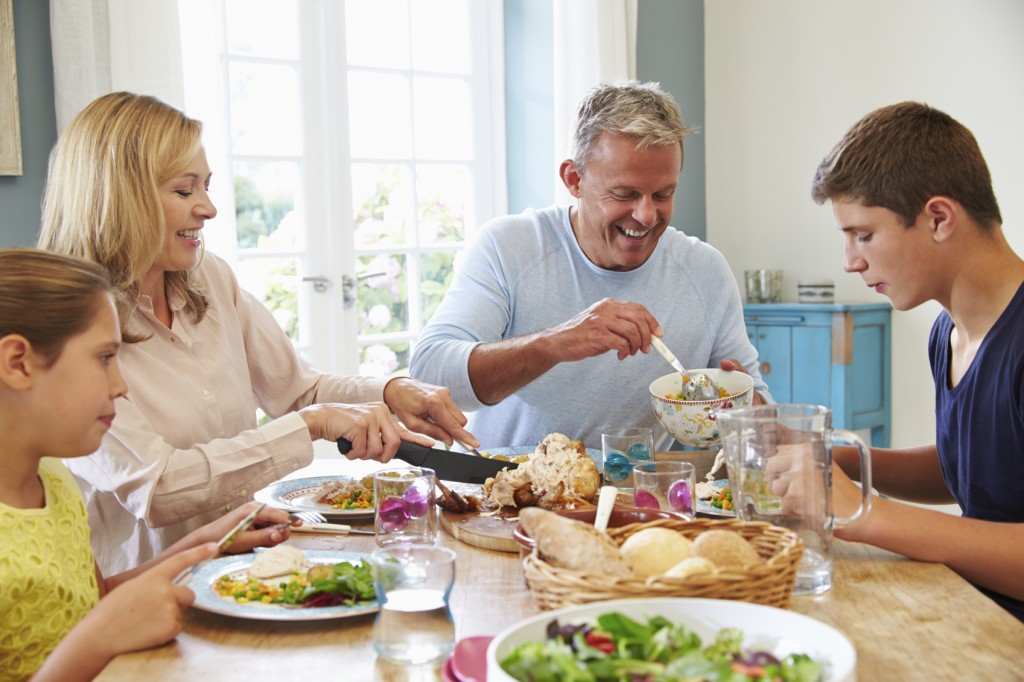 Family Sitting At Table Enjoying Meal At Home Together