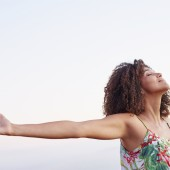 Woman with arms outstretched and her eyes closed outdoors