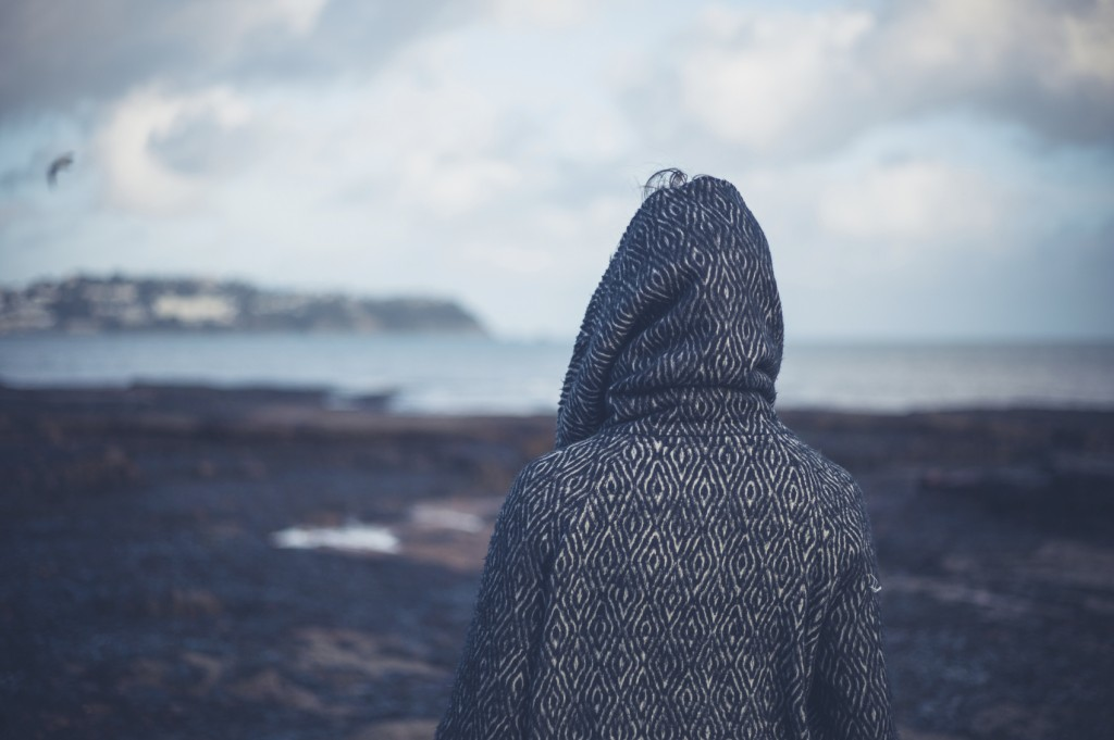 Young woman in hooded coat walking on beach