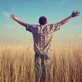 Man with arms raised in field praying