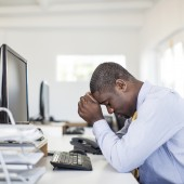 Overworked african businessman sitting at his desk.