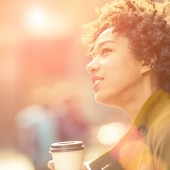 Beautiful woman enjoying coffee outdoors on a sunny autumn day.