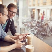 Friends drinking coffee and using smart phones at cafe in city centre. Denmark, Copenhagen.