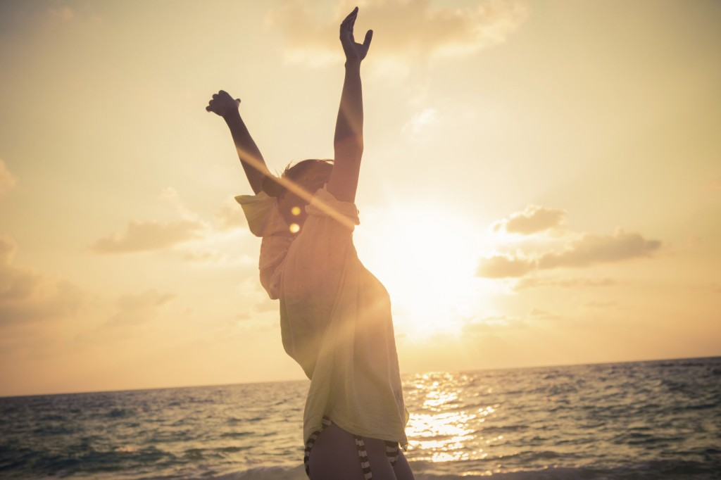 Young woman standing on beach with her arms outstretched