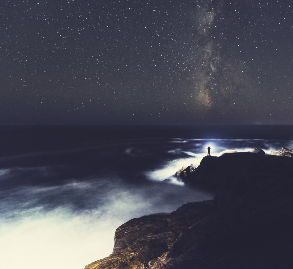 A man stands at the edge of a cliff shining a bright light out into the Atlantic while the Milky Way arcs high above.