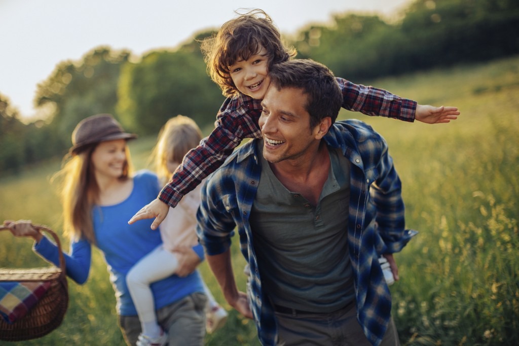 Picture of a young family going for a picnic, walking together threw high grass with the sun in their back.