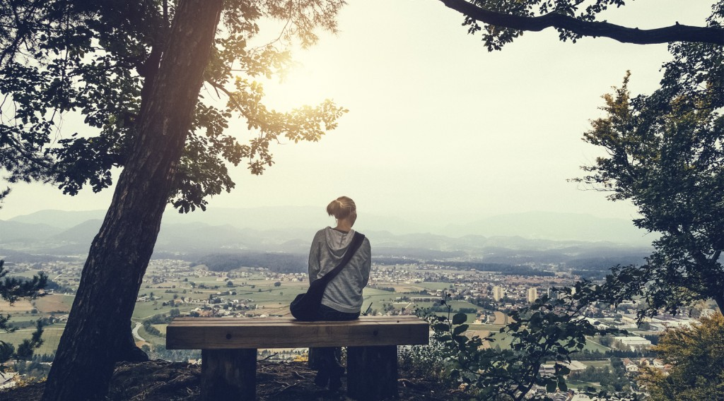 Young woman sitting on bench on top of the hill looking down on her home town.