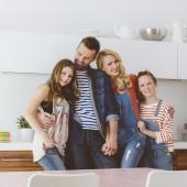 Happy family - mother, father and daughters at home