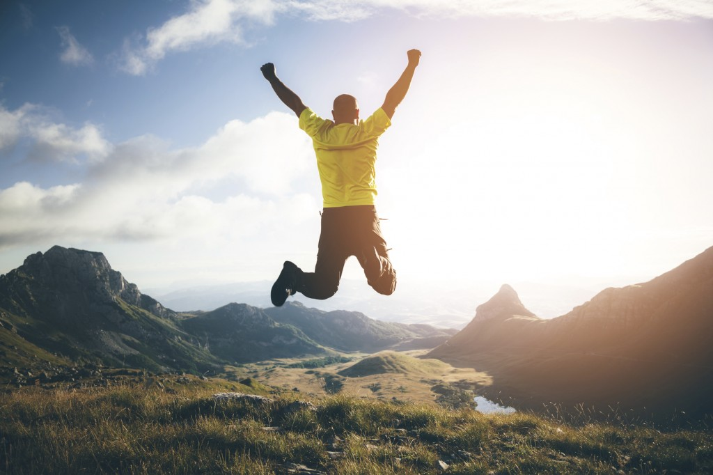 Man jumping in the air on top of the mountain, hands raised up, mountain landscape on background.