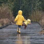 Girl with teddy bear wearing yellow raincoats walking in rain