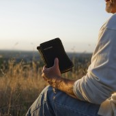 Man praying while holding a Holy Bible in an open field.