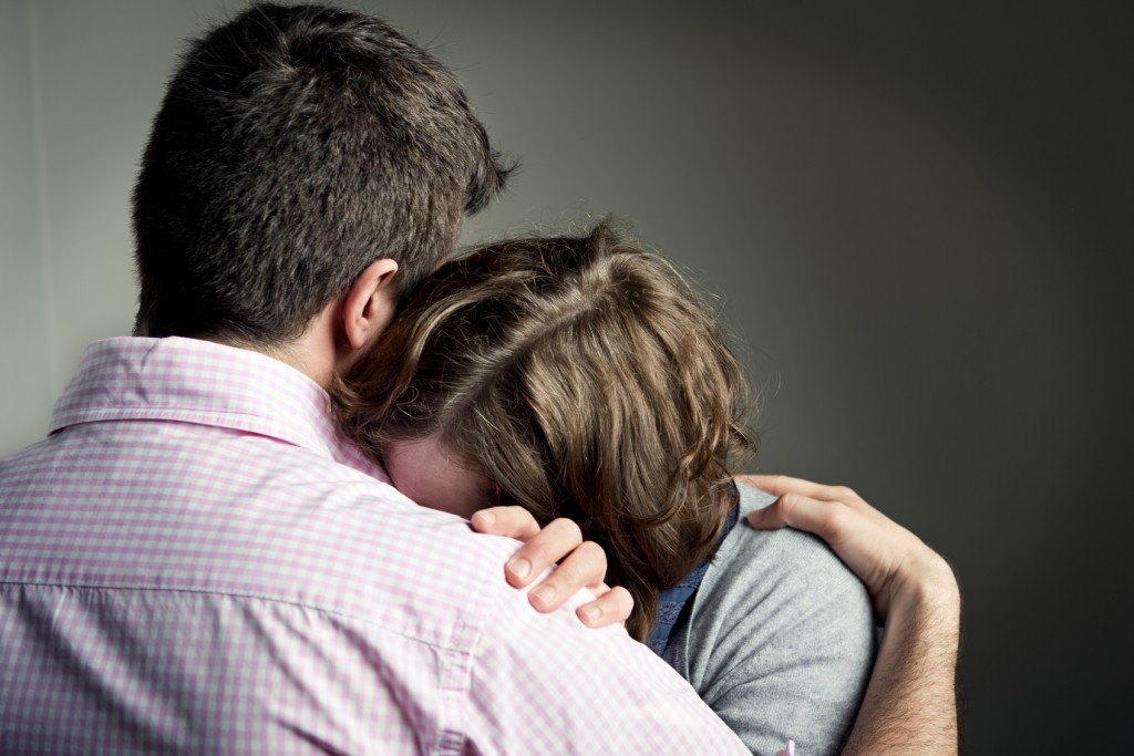 Couple embracing after receiving some bad news.