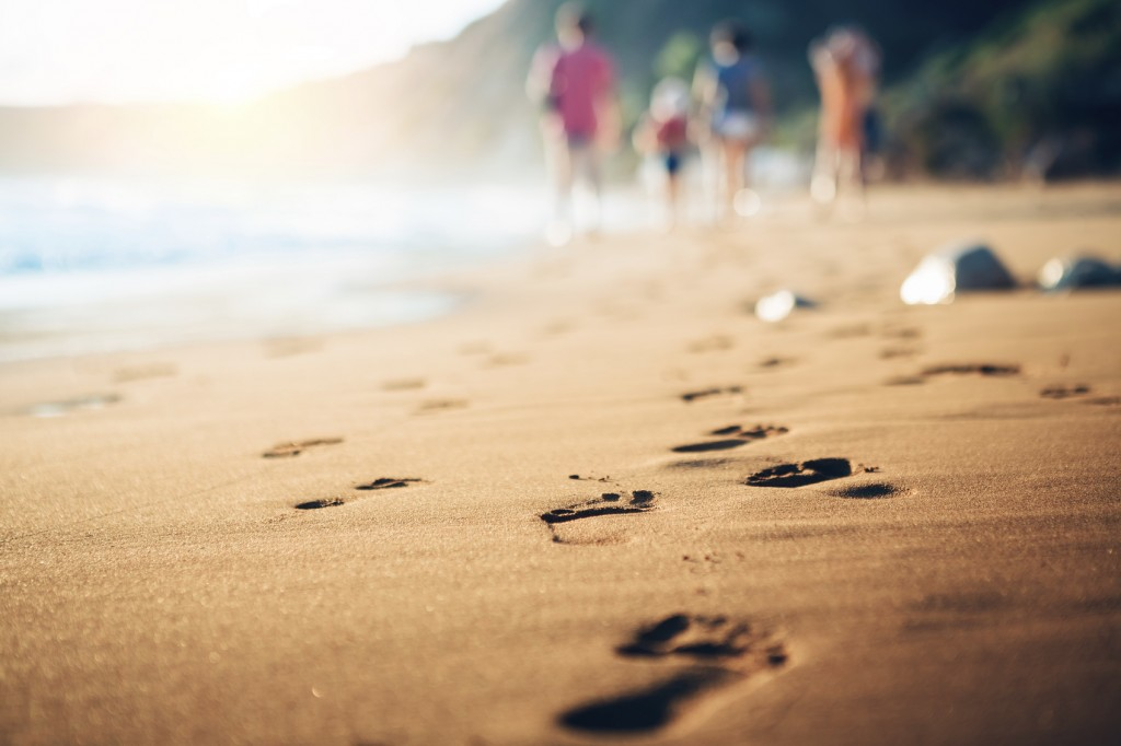 Family walking home from the sandy beach on Kefalonia Island (Avithos). Footsteps in the sand at sunset.