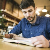 Man Reading Book in Coffee Shop