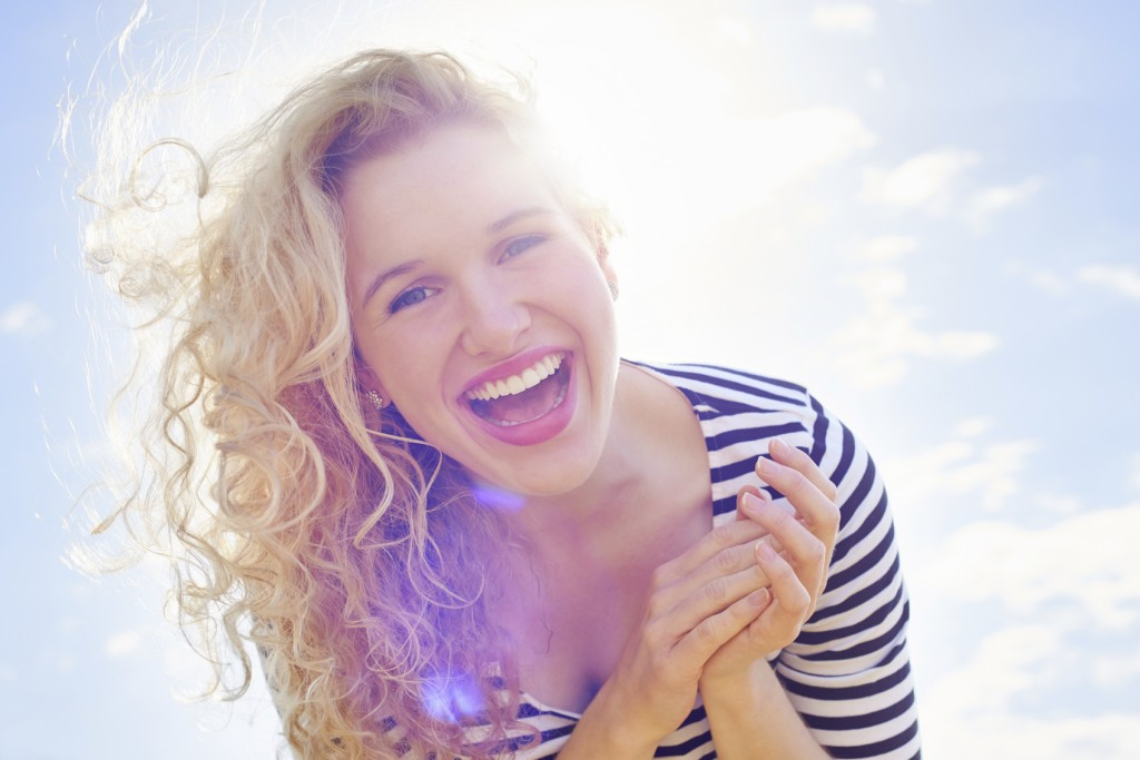 Portrait of an excited young woman standing against a blue