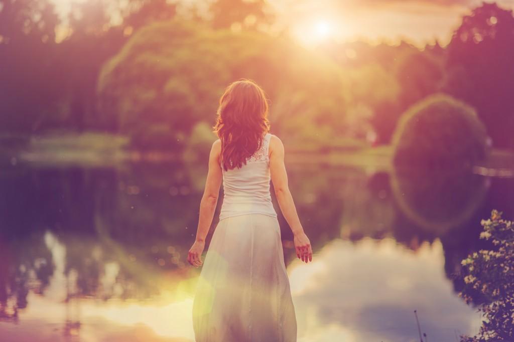 Young beautiful woman enjoying nature in summer evening