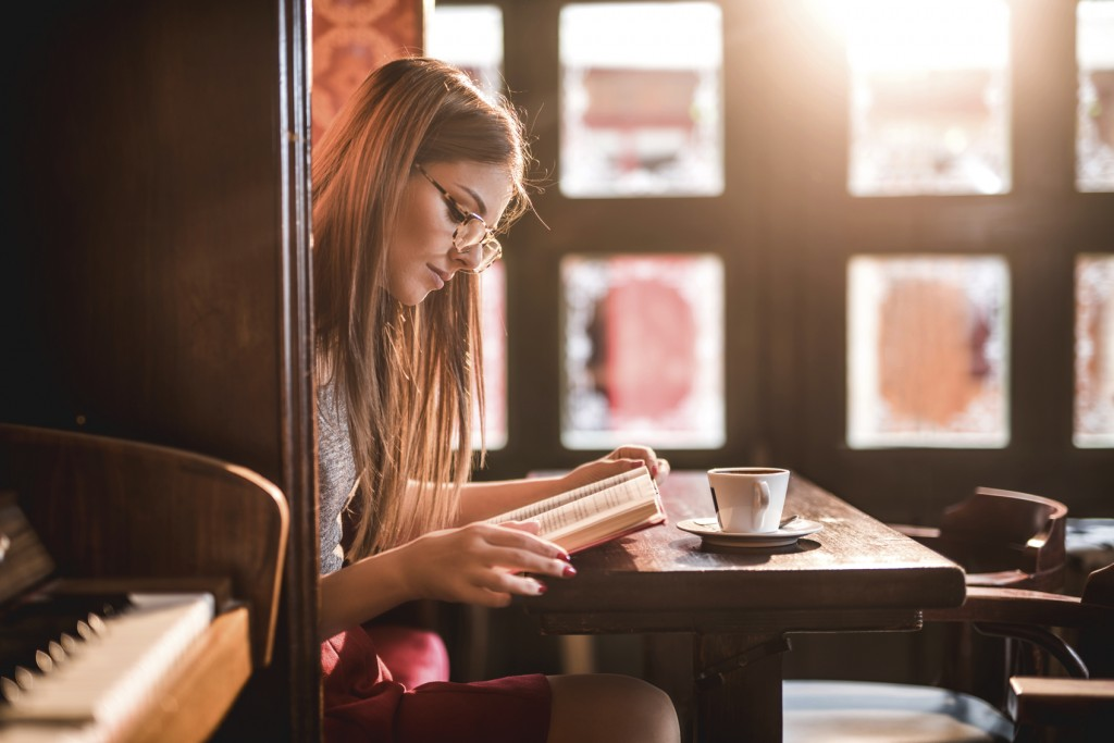 Portrait of young woman having coffee break. She is wearing eyeglasses and studying while sitting alone in coffee shop.