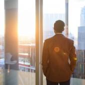 Businessman looking through office window in sunlight