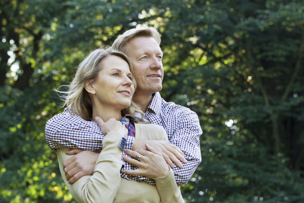 portrait of affectionate mature couple outside in a park looking away