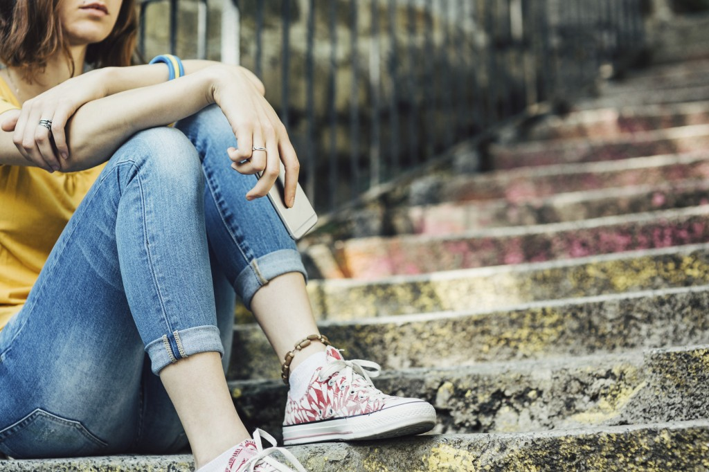 Teen girl dressed in yellow t-shirt sitting on stairs with cell phone