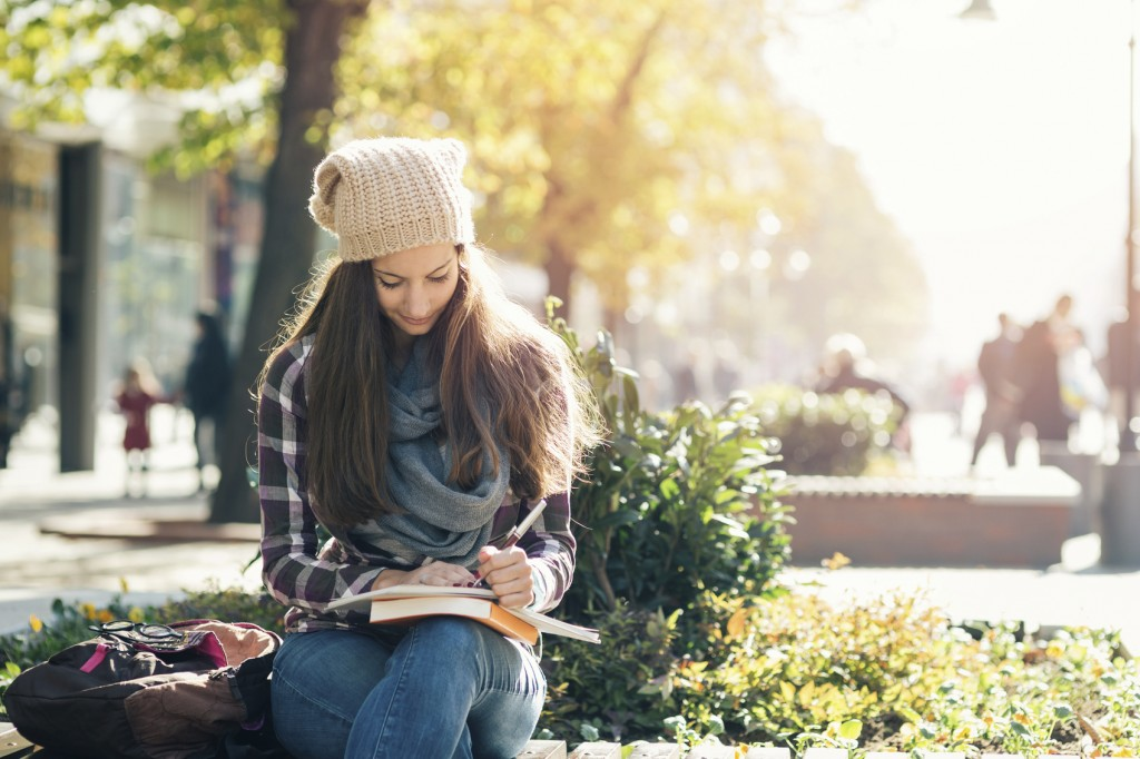 Student girl writing in notebook and studying. Casual clothing, scarf and hat.