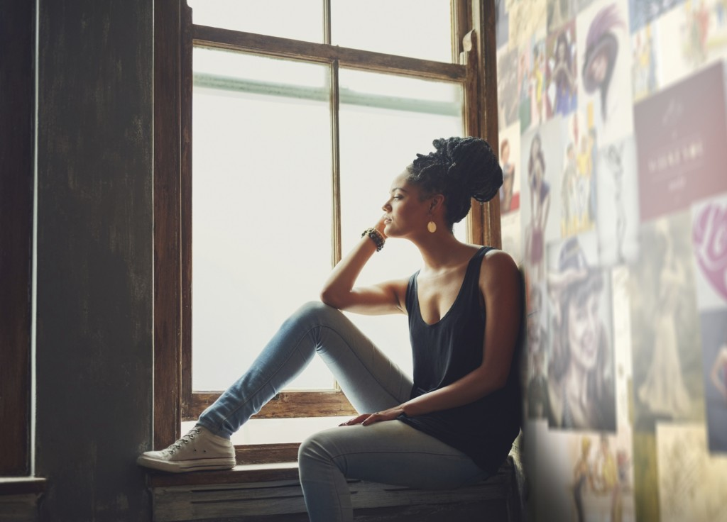 Shot of an attractive young woman sitting by the window