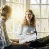 A photo of young woman talking with female friend on window sill. One woman is holding coffee cup while other is with magazine. Bothe are wearing casuals. They are in brightly lit area.