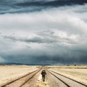Backpacker hiking in between railway tracks in New Mexico. USA.