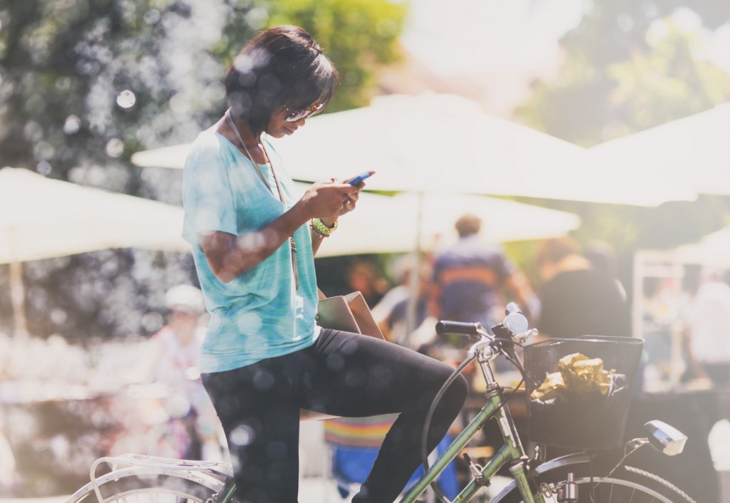 Young woman on her bicycle using phone