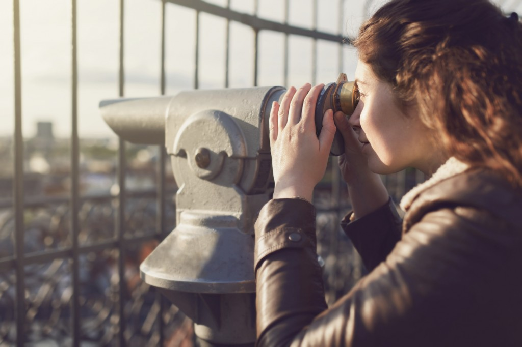 Young caucasian woman looking at the city through a coin operated binoculars, close-up.