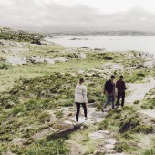 Three young adults walking near the sea in Norway