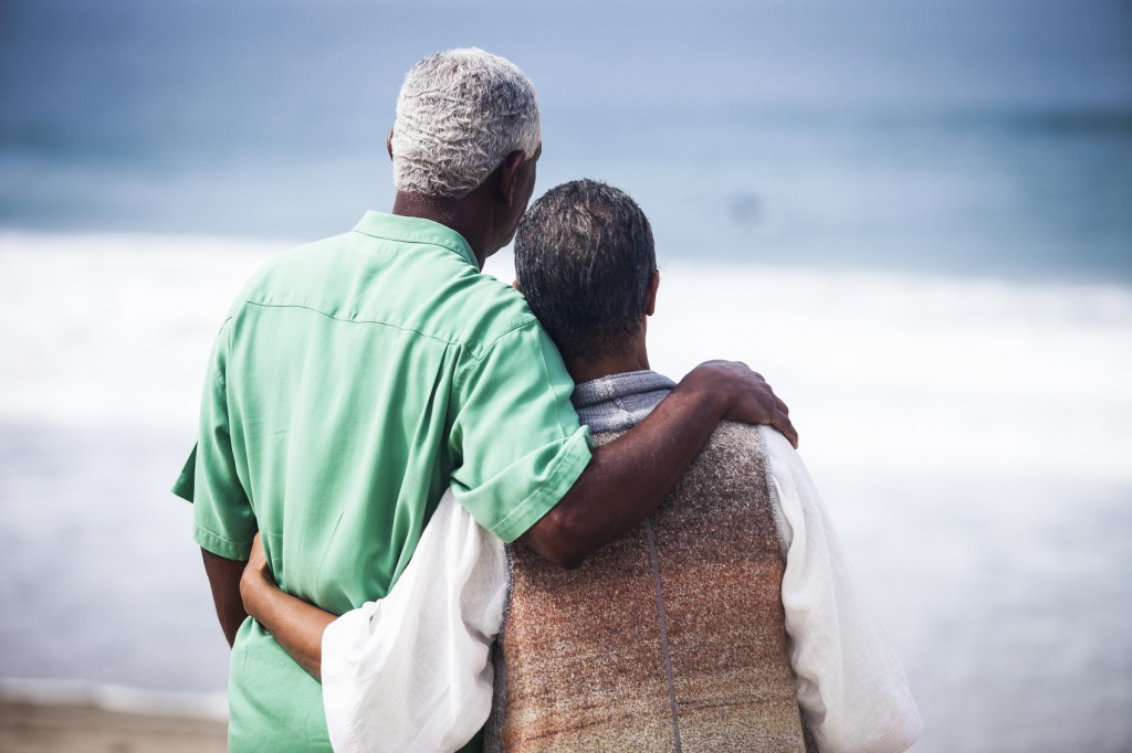 Senior African American couple together on the beach, from behind.