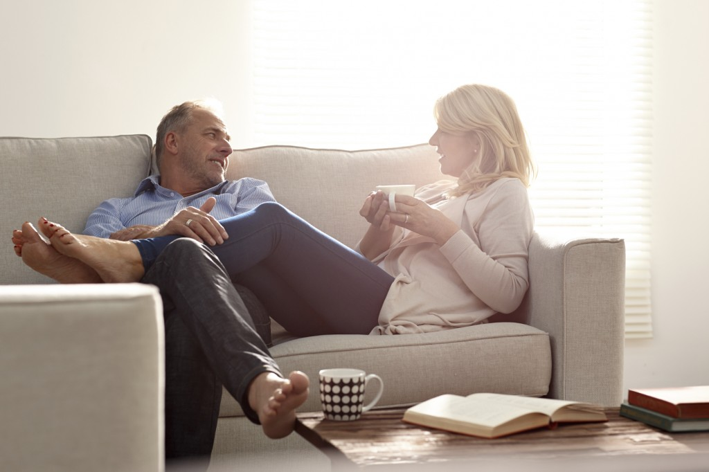 Couple talking in living room with coffee