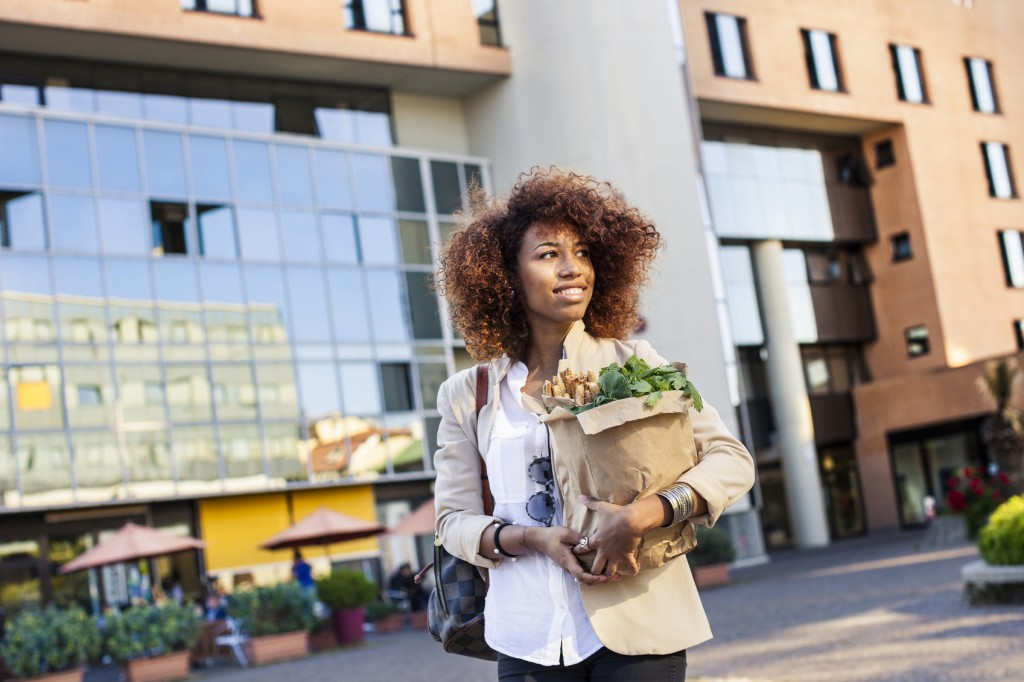 Young afro woman holding a shopping bag full of green vegetables and sesame breadsticks walking in the morning before going at work.