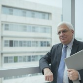 Smiling confident businessman standing at the office window and looking at the camera
