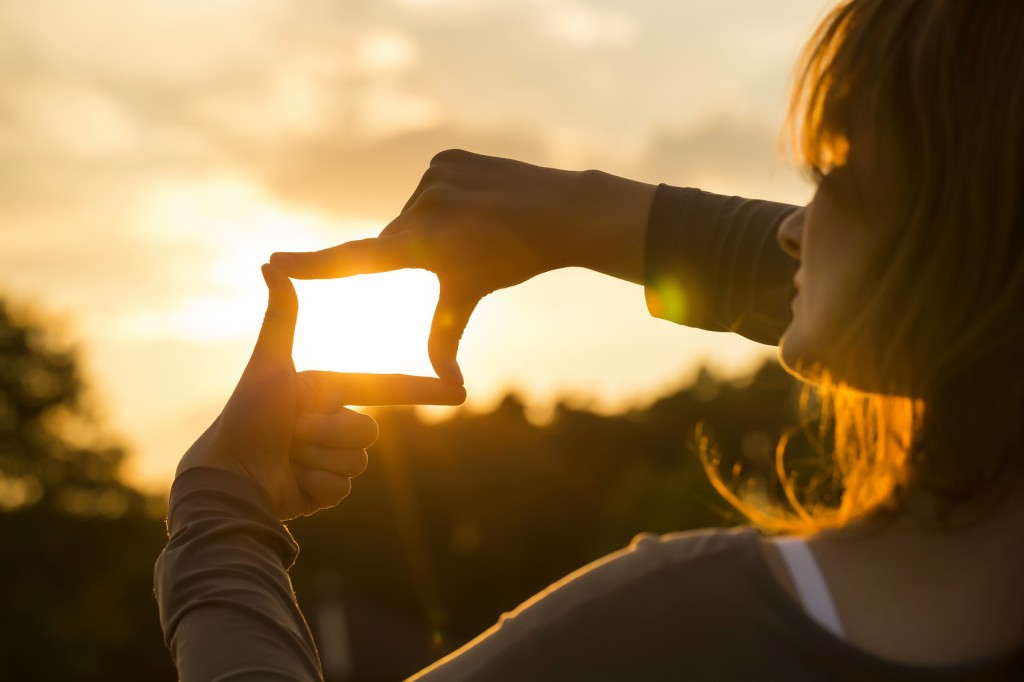 woman capturing the sunset with fingers frame