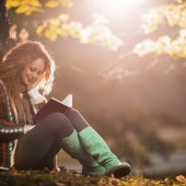 Young woman relaxing while reading a book at the park.