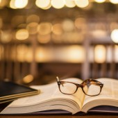 Close-up of reading glasses and digital tablet on book in library.