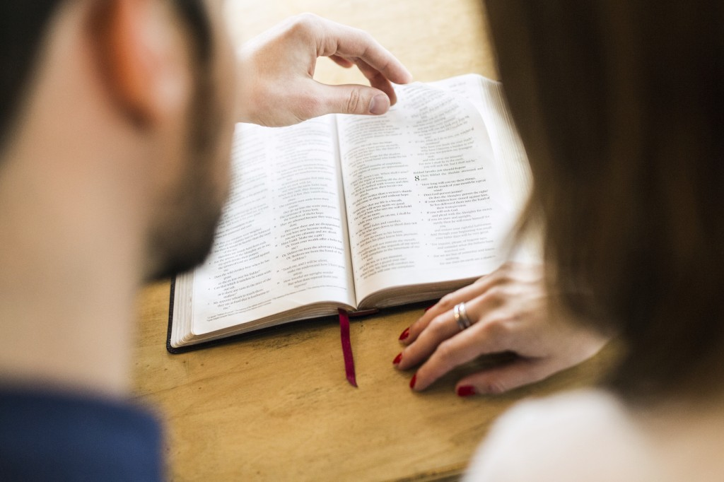 An adult man and woman study the Bible together, sharing their favorite scriptures while enjoying a cup of coffee. The husband reads aloud while pointing out a verse to his wife. Shot as viewed from behind and over their shoulders, the focus on the scripture in the background.