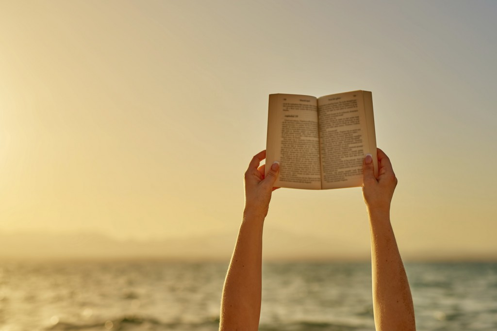 unrecognizable woman hands holding book at sunset with the sea side in background.