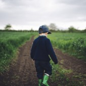 Photo of a little boy walking on a dirt road, spending time in nature