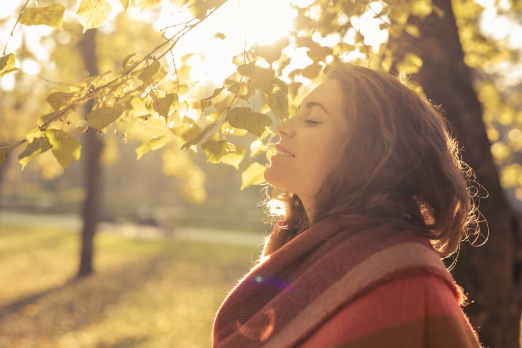 Beautiful, young, caucasian woman standing in the park and enjoying with her eyes closed